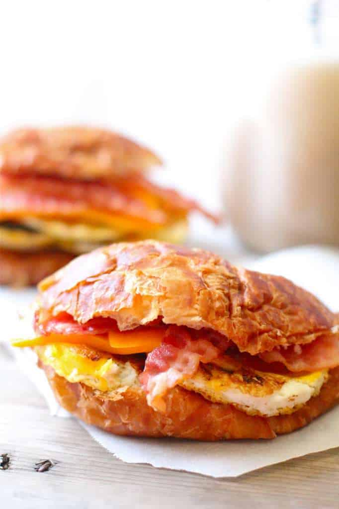 closeup of croissant breakfast sandwiches containing bacon, eggs, and cheese