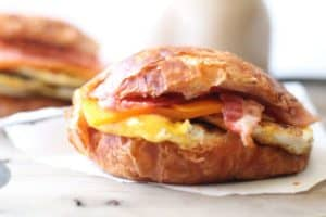 closeup of croissant breakfast sandwiches on a white napkin