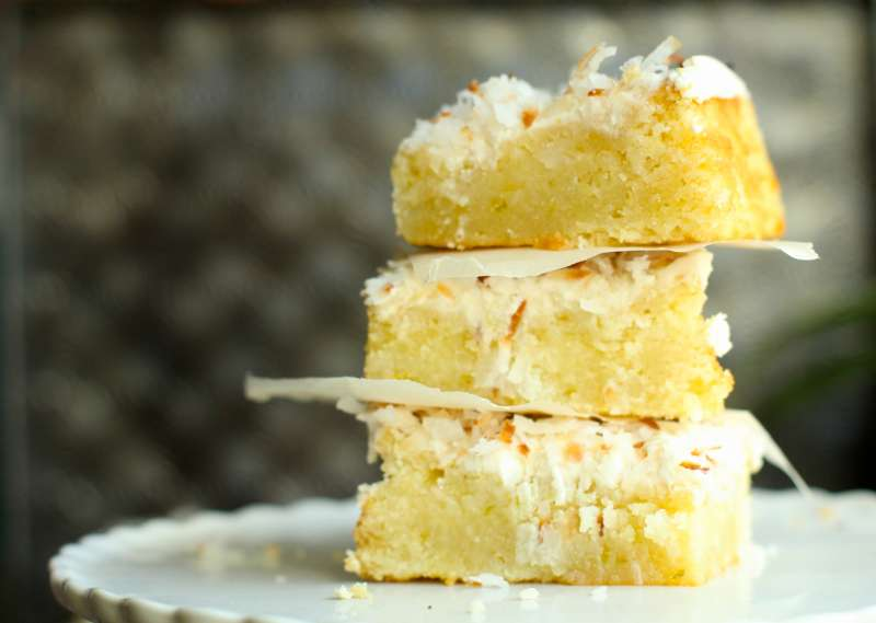Luscious lemon brownies topped with coconut butter cream and toasted coconut