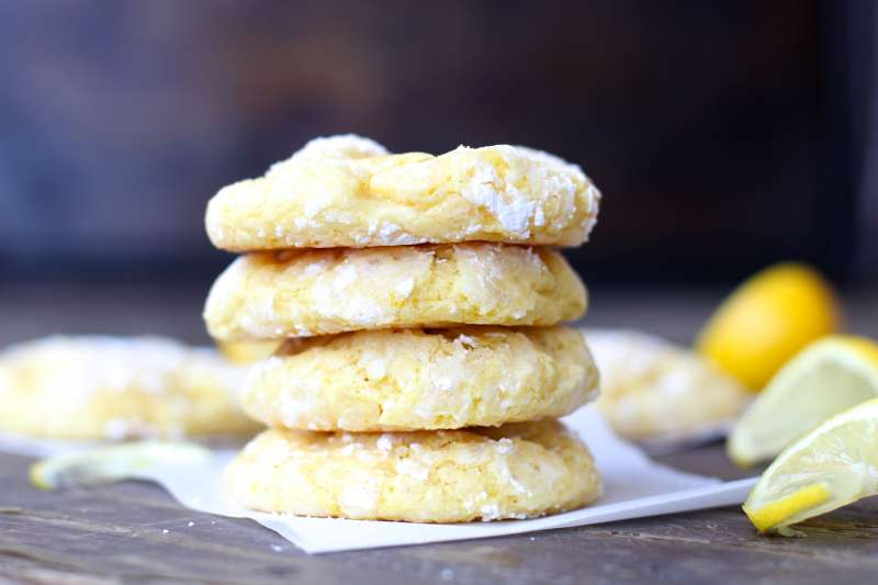 side shot of four stacked Lemon Bar Cookies next to lemon wedge