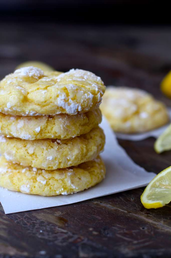 closeup of several lemon bar cookies on parchment paper on a wooden background
