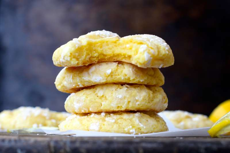 four Lemon Bar Cookies stacked with the top lemon bar cookie missing a chunk