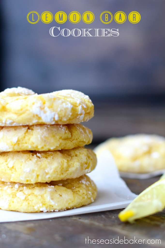 four lemon bar cookies stacked on a white napkin next to a sliced lemon