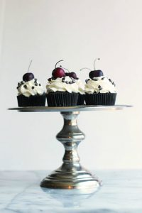 Chocolate cupcakes studded with chopped cherries and topped with fresh whipped cream and more chocolate.