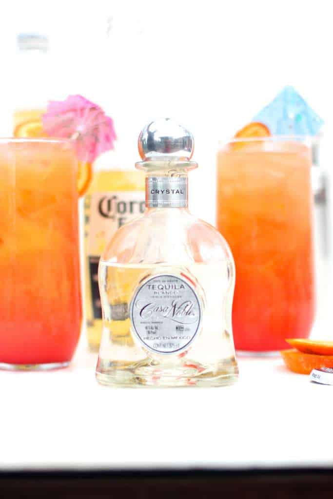 closeup of tequila bottle in front of corona cocktail glasses