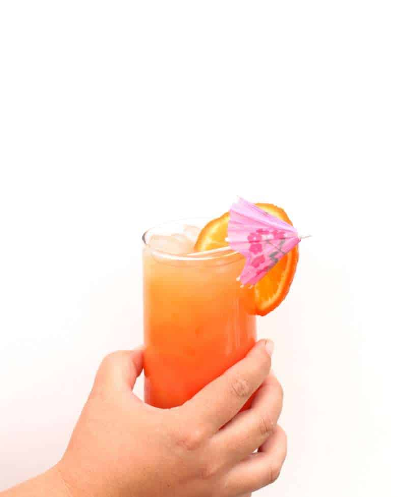 hand holding a corona cocktail with an orange slice over the side and a purple umbrella