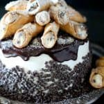 Layered cake with rich ricotta cannoli filling topped with an italian buttercream and homemade mini cannolis