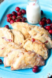 several hand pies on a blue plate next to cherries and a glass of milk