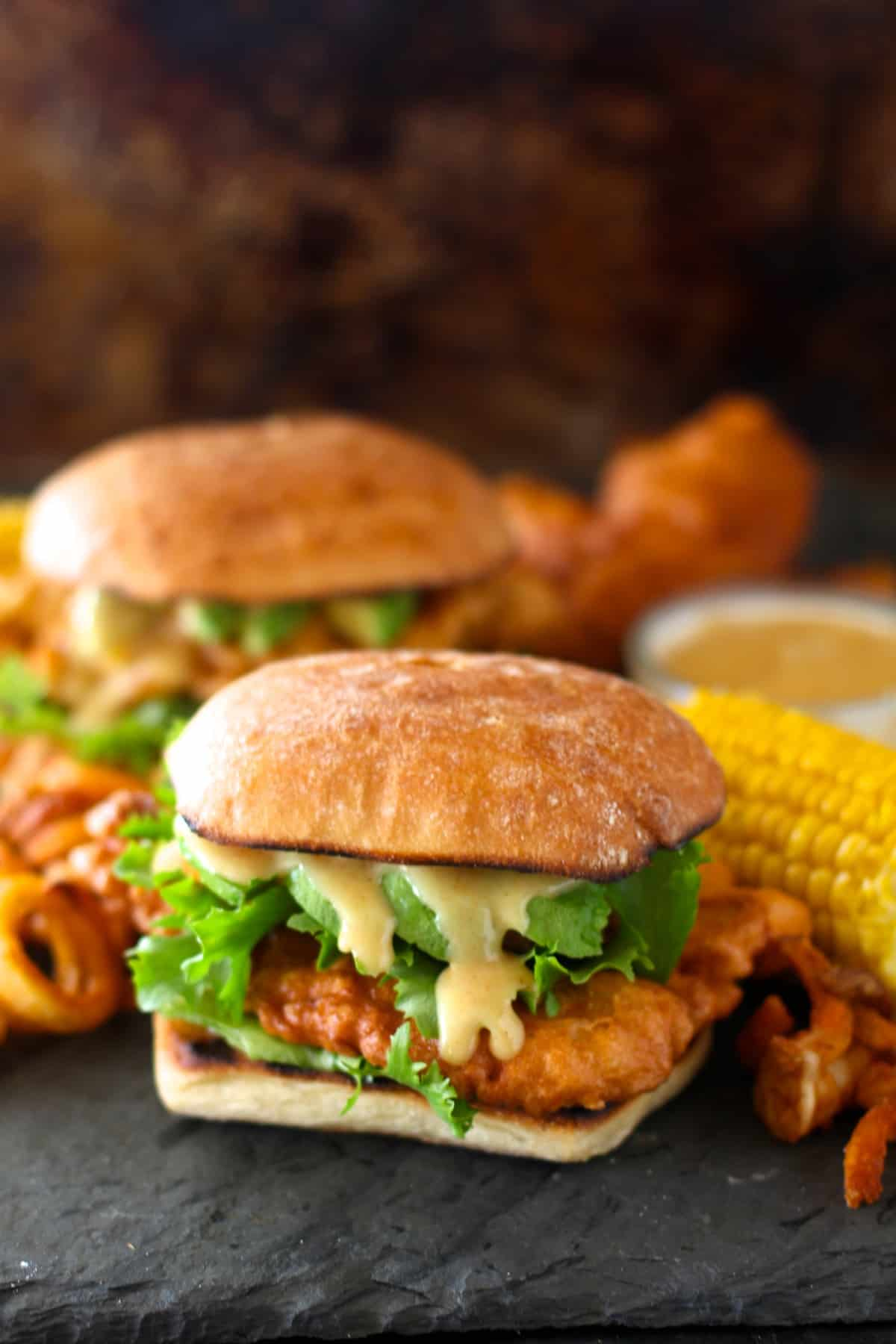 front view of copycat chili's chicken crispers in a sandwich with lettuce and honey mustard