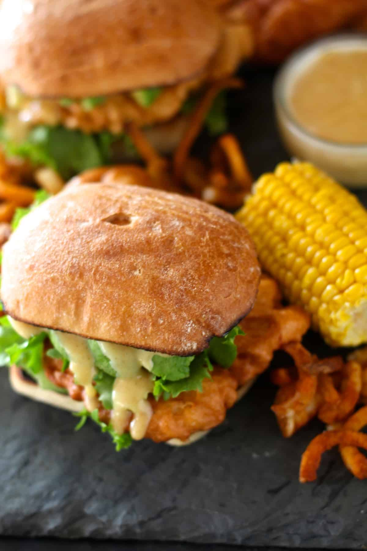 overhead shot of copycat chili's chicken crispers in a sandwich on a black table next to an ear of corn