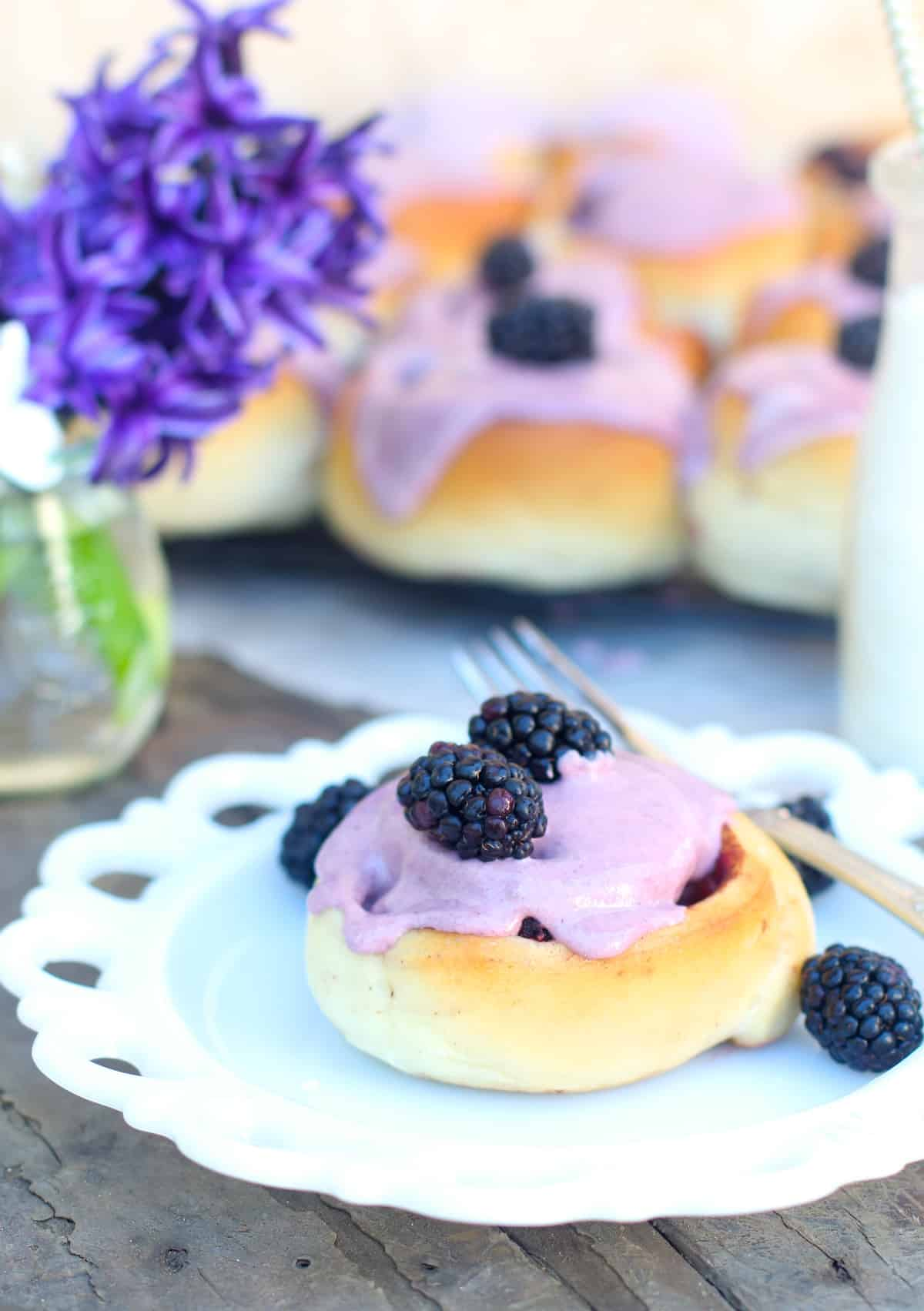 Soft sweet rolls with cinnamon and fresh blackberries topped with cream cheese blackberry icing