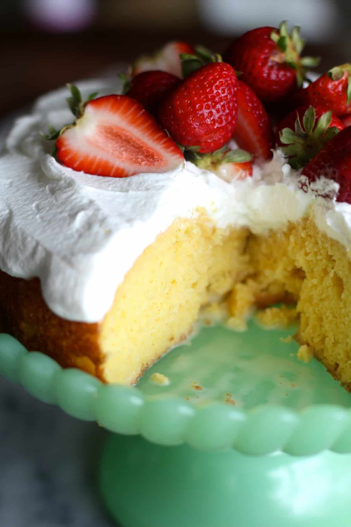 closeup of easy tres leches cake with whipped cream and strawberries on top