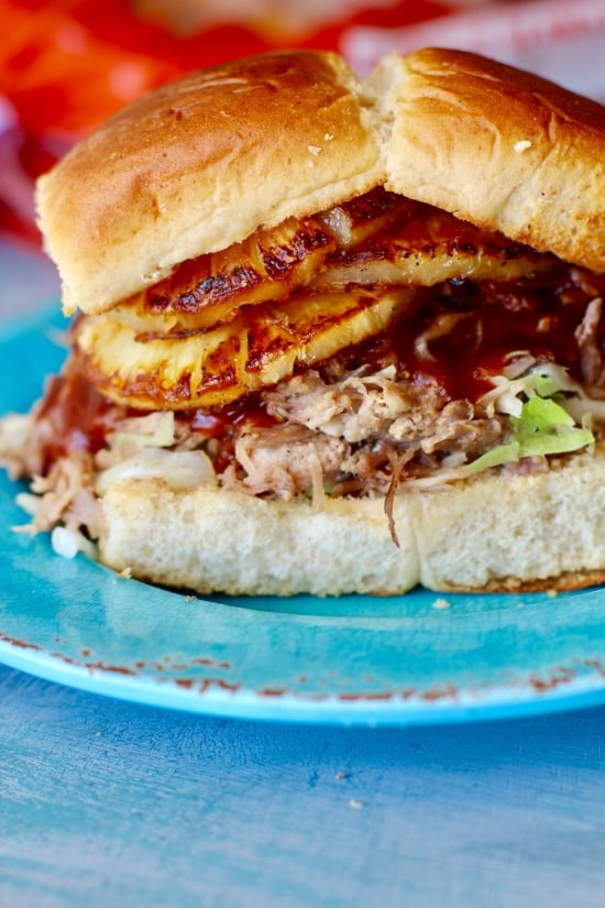 Easy Slow Cooker pork that is tender and shreds with a fork. Served on Hawaiian Sweet Bread with Teriyaki sauce and pineapple and perfect for serving a crowd!