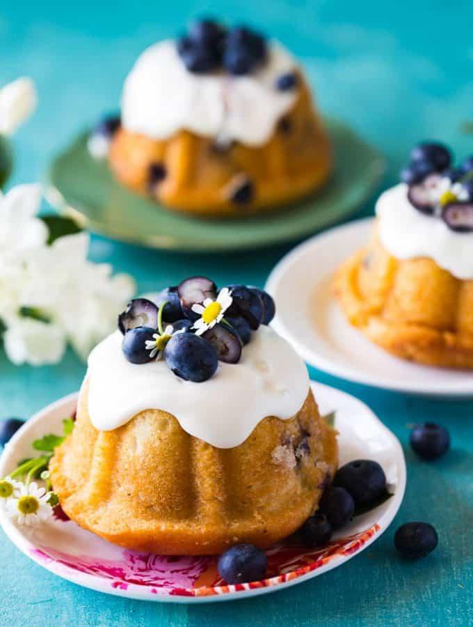 three mini blueberry bundt cakes on individual serving plates