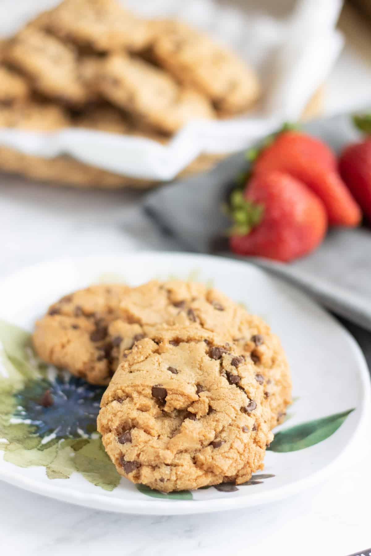 closeup of chocolate chip strawberry cookies on a plate with another basket in the background