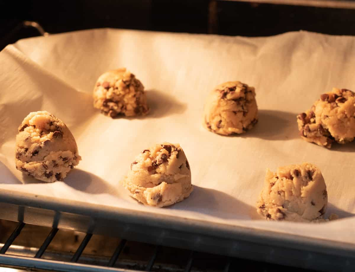 raw chocolate chip strawberry cookies inside the oven on parchment paper