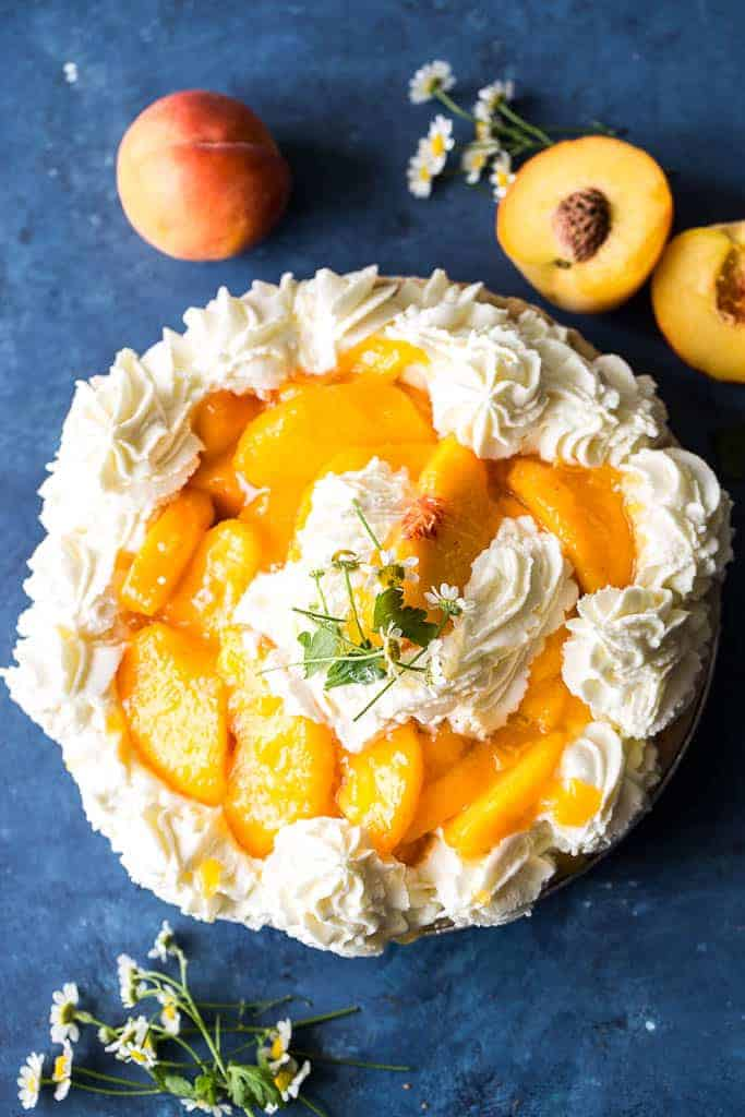 overhead view of fresh peach pie surrounded by raw peaches