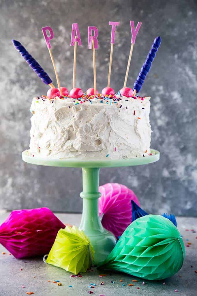 funfetti cake on a green cake stand with PARTY text on the top