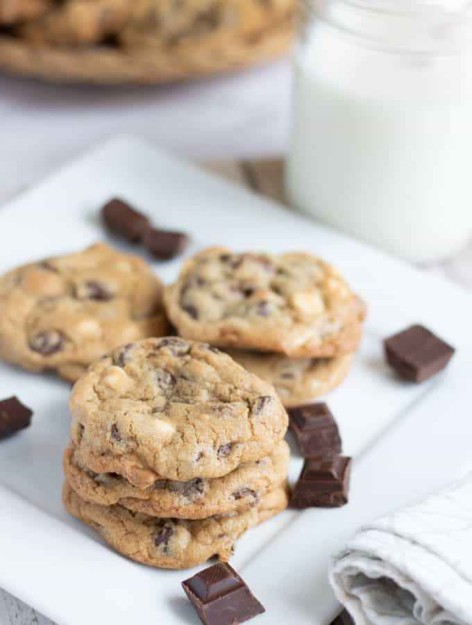 Triple Chocolate cookies on a white plate next to a glass of milk