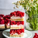 raspberry cream cheese bars stacked on a plate