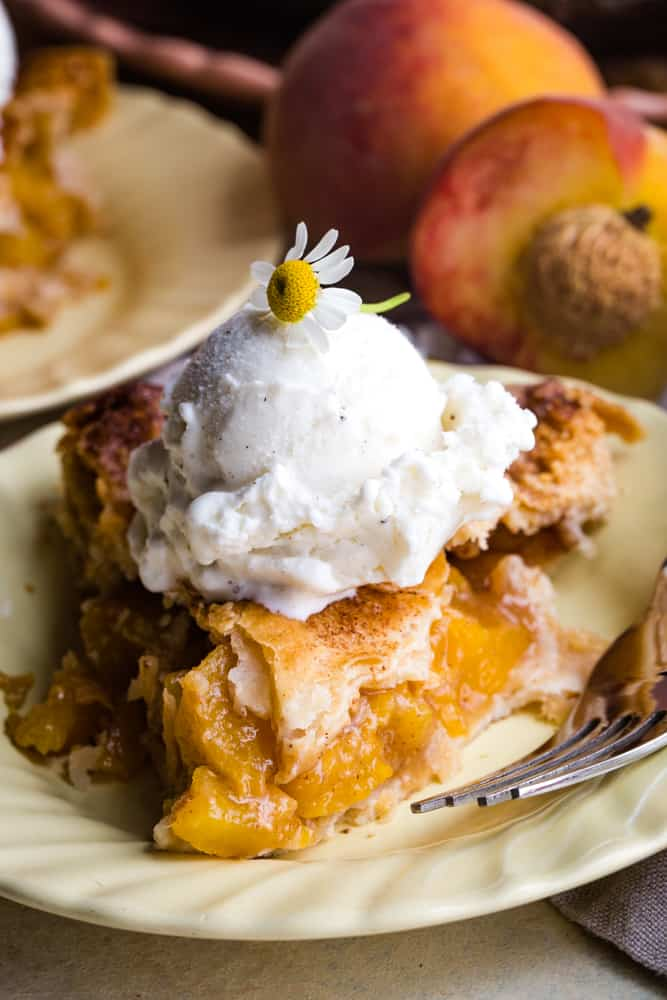 slice of caramel peach pie with scoop of ice cream