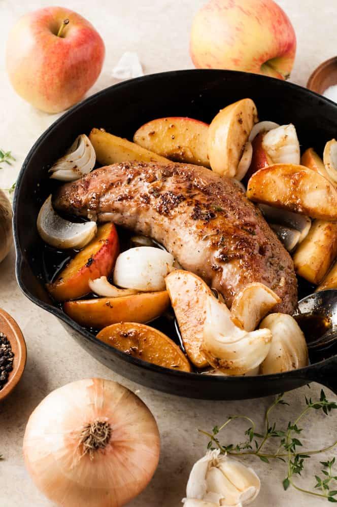cooked pork tenderloin with apples in pan