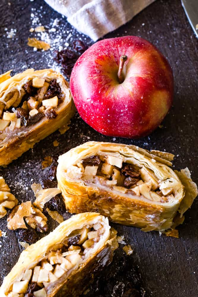 slices of apple strudel with phyllo dough next to a red apple