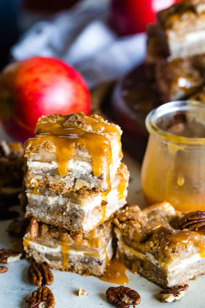 caramel apple cheesecake bars stacked with apple background
