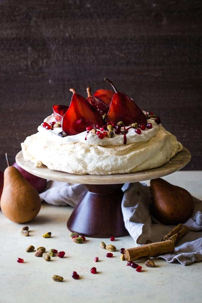 cake stand with pavlova with pomegranate pears
