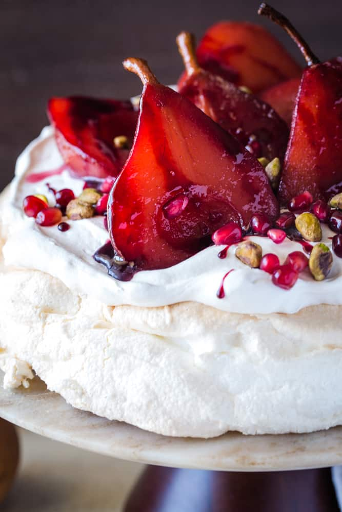 close up shot of pavlova with pomegranate pears