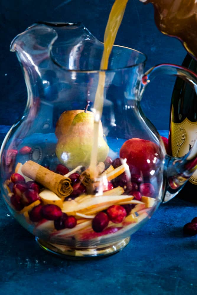 pouring champagne into pitcher filled with fruit