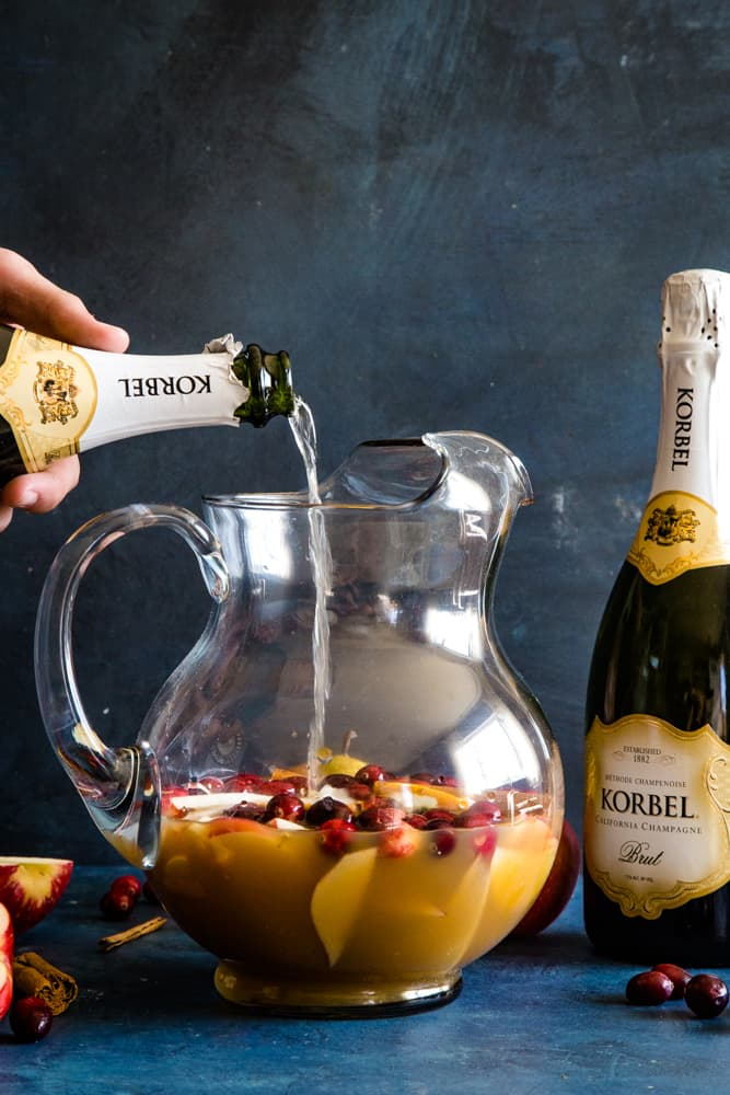 pouring korbel champagne into pitcher with fruit
