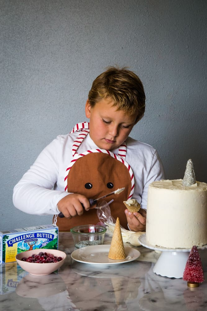 boy decorating cranberry christmas cake