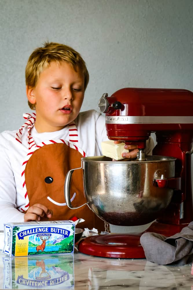 boy putting butter into mixing bowl to make cranberry christmas cake