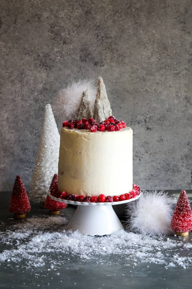 cranberry spice cake on cake stand with trees in background