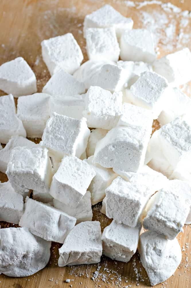 cutting board with a bunch of cut vanilla marshmallows