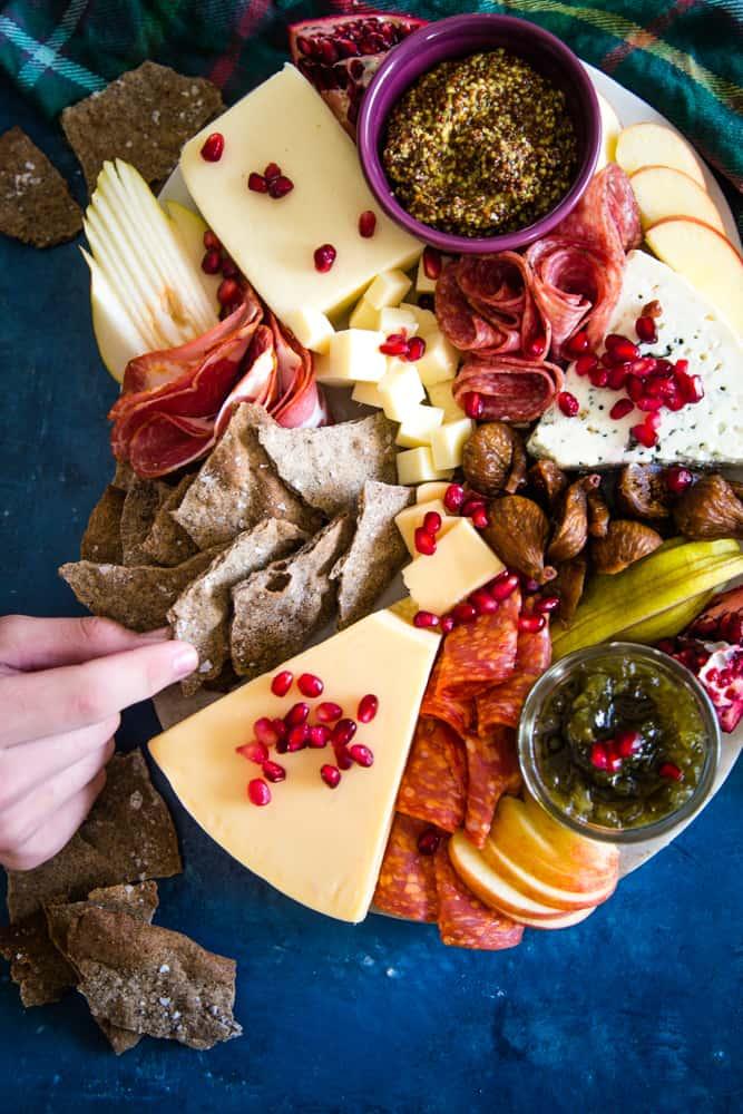 hand grabbing a buckwheat cracker on cheeseboard