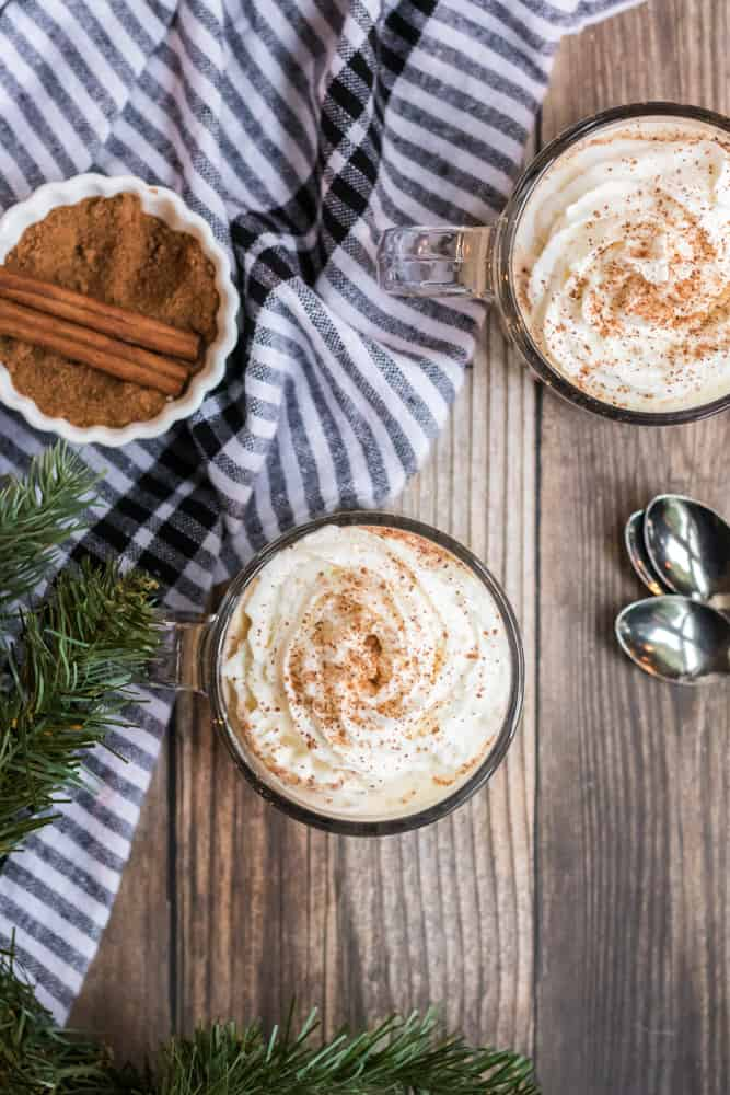 eggnog recipe topped with whipped cream and bowl of cinnamon sticks