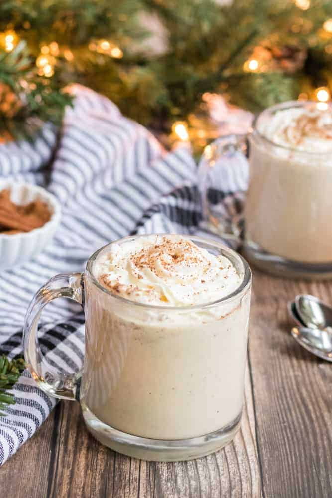 cup of eggnog recipe in two glasses with Christmas tree in background