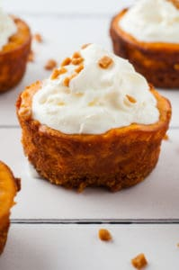 mini pumpkin cheesecakes on white wood board
