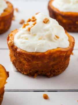 mini pumpkin cheesecakes on white wood board