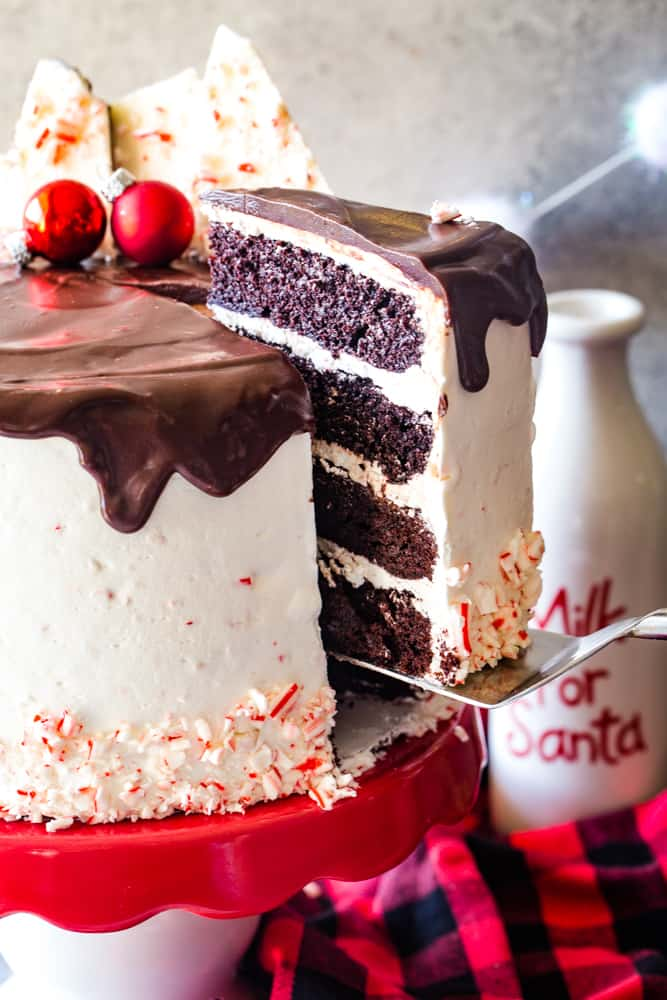 taking a slice of peppermint bark layer cake