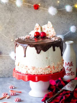 peppermint bark layer cake on red and white cake stand