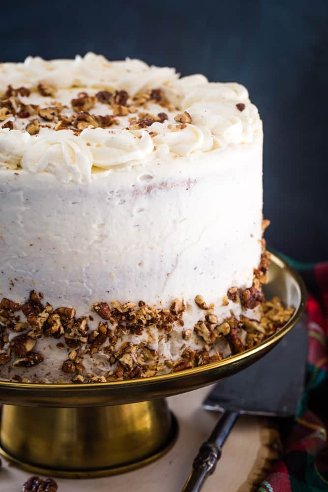 eggnog layer cake with candied pecans on gold cake plate