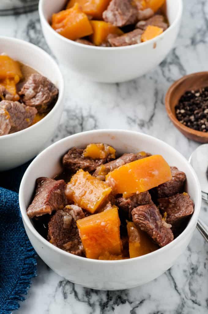 butternut squash beef stew in white bowls