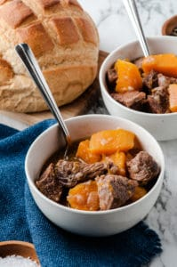 butternut squash beef stew in white bowls with spoons and bread