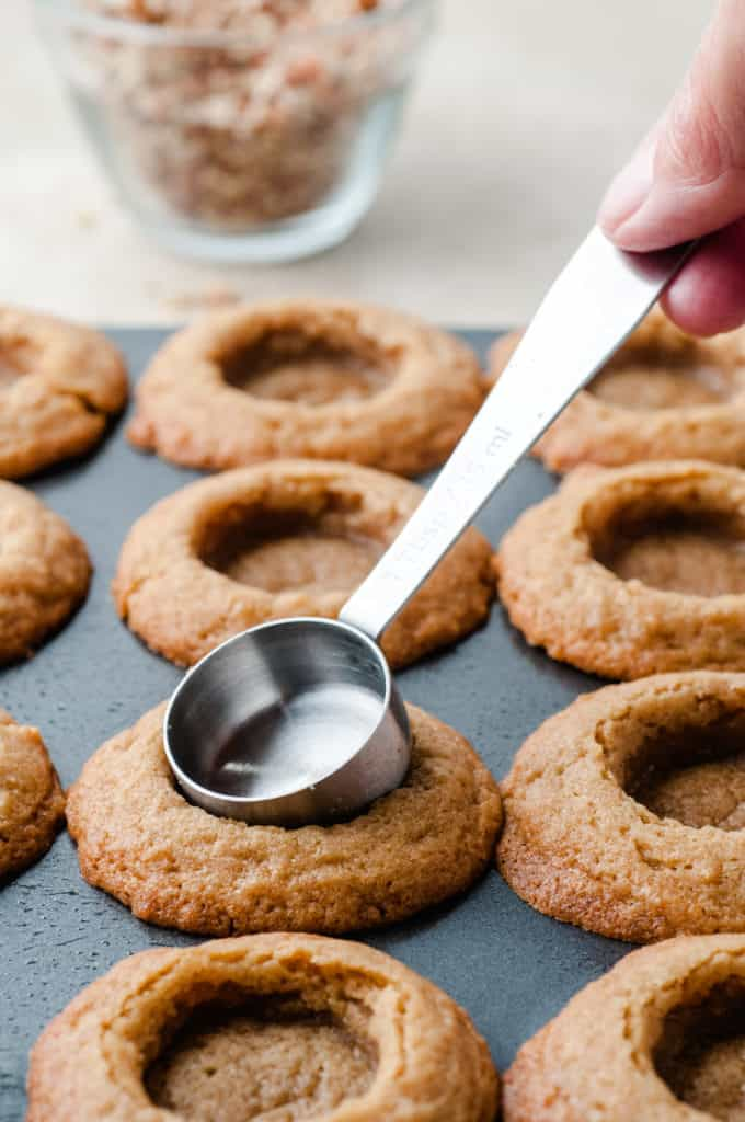using measuring spoon to make indents in caramel pecan cookie cups