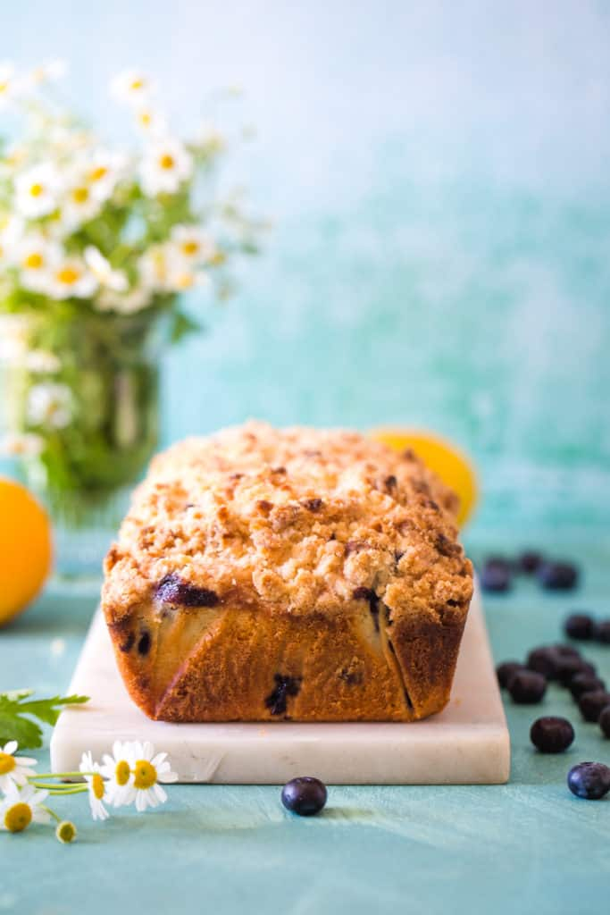 loaf of blueberry lemon streusel bread on white cutting board with flowers in the background