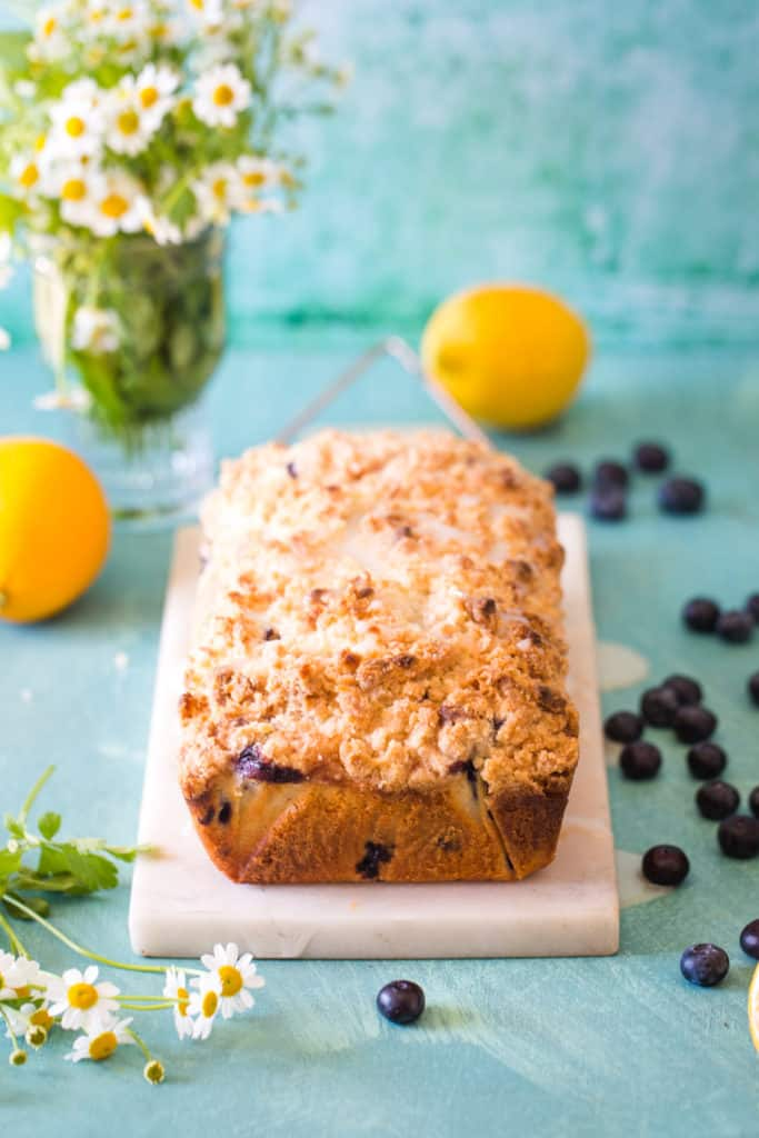 lemon blueberry loaf on white marble with flowers in background