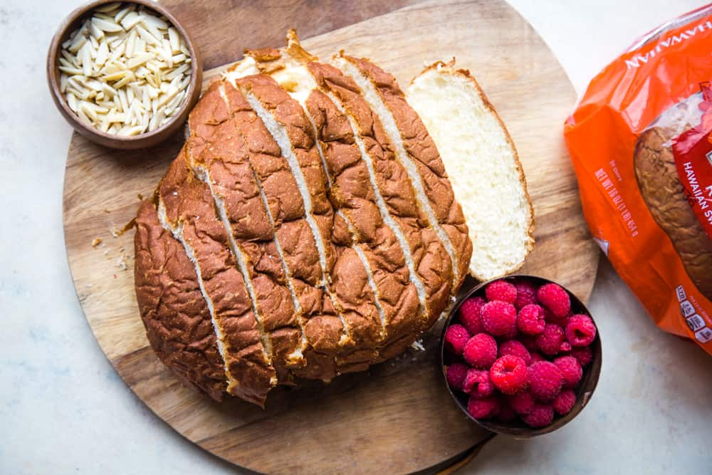 sliced round bread on cutting board with bowl of almonds and raspberries